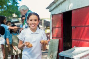 Student holding eggs in chicken coop during farm field trip